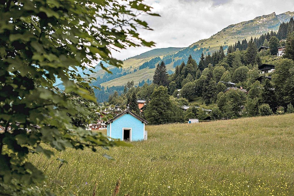 A pretty blue Church in a grassy field in Saalbach Hinterglemm Austria