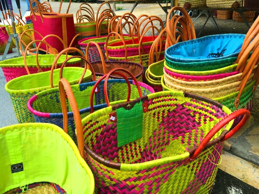 A photo of colourful french picnic baskets. Picnicking your way around France is a budget travel tip from Travel Bloggers.